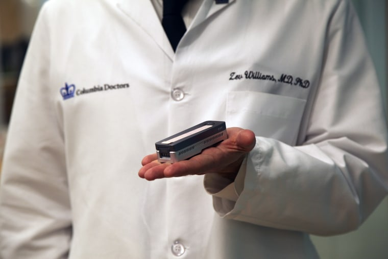The device Dr. Zev Williams uses for genetic testing looks like a miniature stapler.