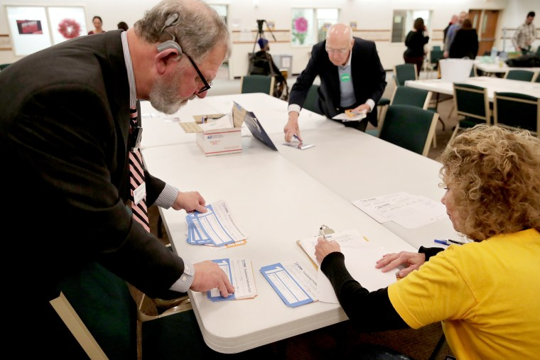 Image: Precinct workers tally Iowa Democratic Caucus votes by hand as caucus results are counted after a Democratic presidential Caucus in West Des Moines, Iowa
