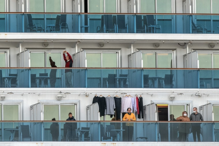 Image: A passenger jogs on the spot as another stretches as they wait on the balconies of their cabins on the Diamond Princess cruise ship as it sits docked at Daikoku Pier