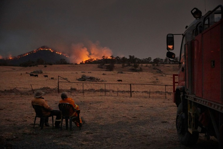 "Image: Rural Fire Service volunteer firefighters watching as the New South Wales ""megafire"" approaches the outskirts of the town of Tumbarumba in New South Wales"