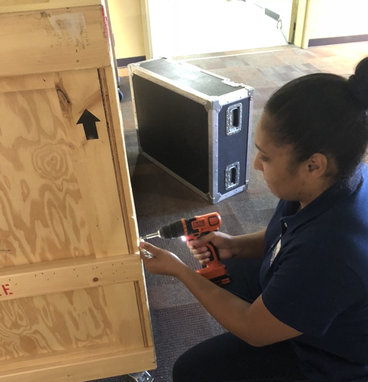Fazande works to assemble a crate that will carry exhibit displays to different museums across the country.