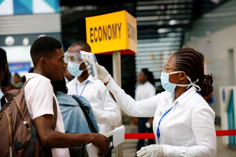 Image: A health worker checks the temperature of a traveler as part of a coronavirus screening procedure at the Kotoka International Airport in Accra, Ghana, on Jan. 30, 2020.