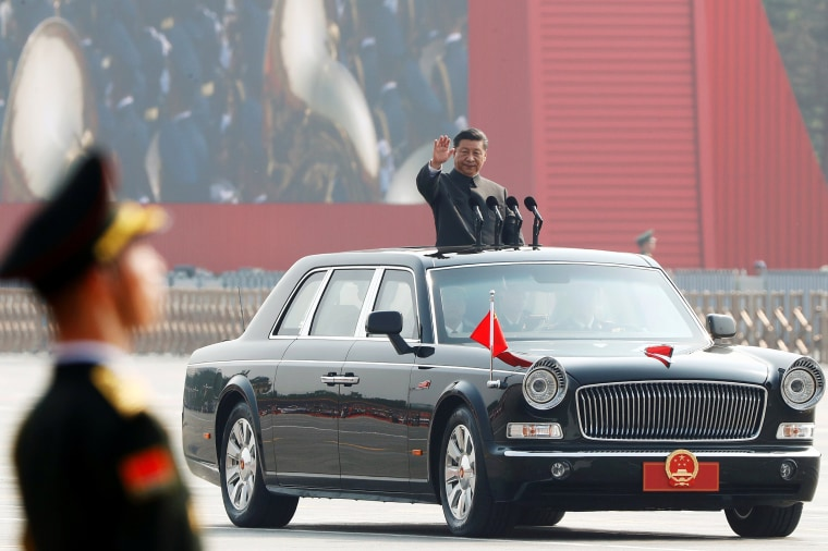 Image: Chinese President Xi Jinping waves from a vehicle as he reviews the troops at a military parade marking the 70th founding anniversary of People's Republic of China