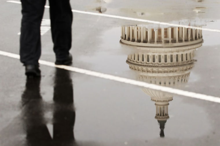 The dome of the U.S. Capitol Building is reflected in a puddle on a rainy morning in Washington