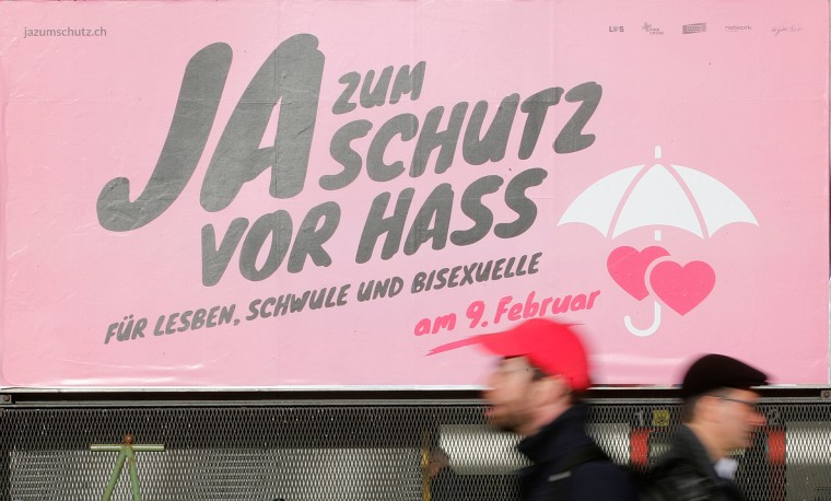 Image: People walk past a poster demanding protection from hate speech in Zurich