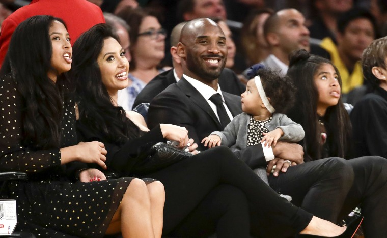 Former Los Angeles Laker Kobe Bryant watches a tribute video with his family during an NBA game between the Los Angeles Lakers and the Golden State Warriors in Los Angeles on Dec. 18, 2017.
