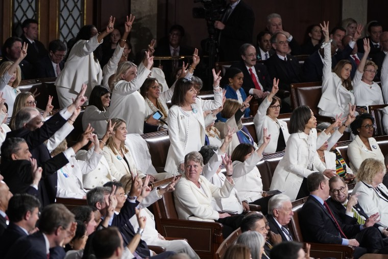 Democratic members of Congress wearing white, hold up three fingers for the HR3 health care bill