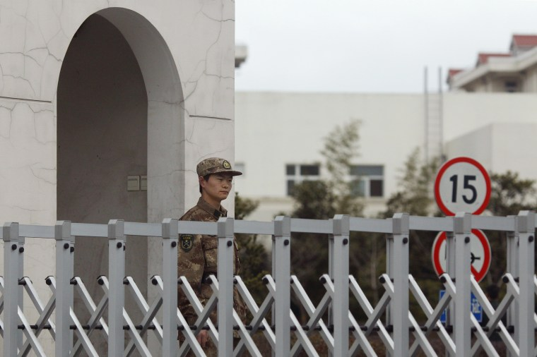 A Chinese People's Liberation Army soldier stands guard in front of 'Unit 61398' in the outskirts of Shanghai