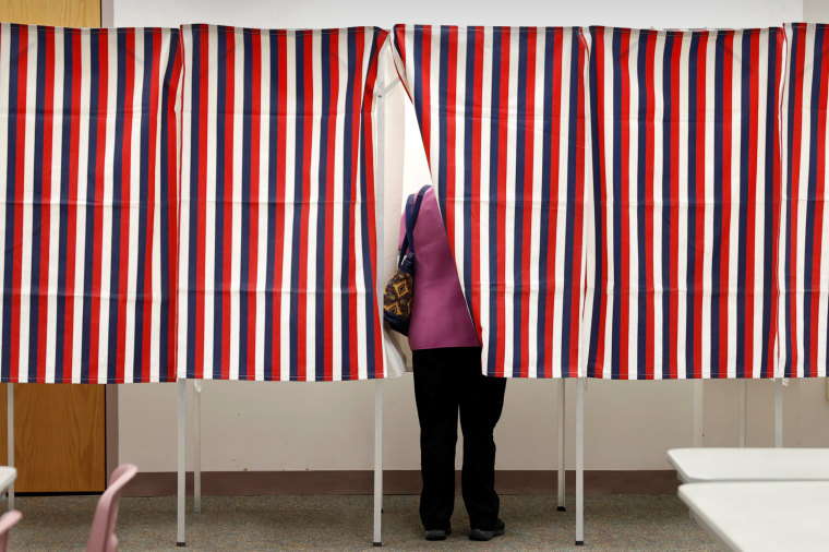 Image: A voter stands in voting booth while voting in the New Hampshire U.S. presidential primary election in Manchester