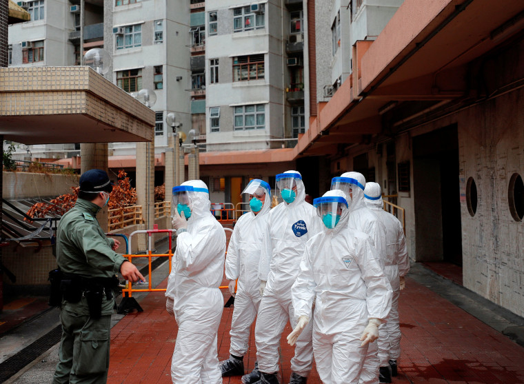 Image: Police in protective gear wait to evacuate residents from a public housing building, following the outbreak of the novel coronavirus, in Hong Kong