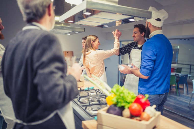 Image: Young couple enjoying cooking class in kitchen