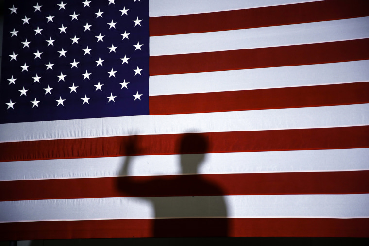 Image: Pete Buttigieg's shadow is cast on an American flag at a campaign event in Plymouth, N.H., on Feb. 10, 2020.
