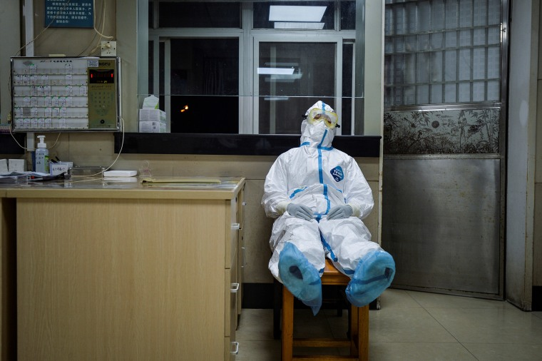 Image: A medical worker in protective suit takes a break during her night shift at a community health service center in the Qingshan district of Wuhan, Hubei province.