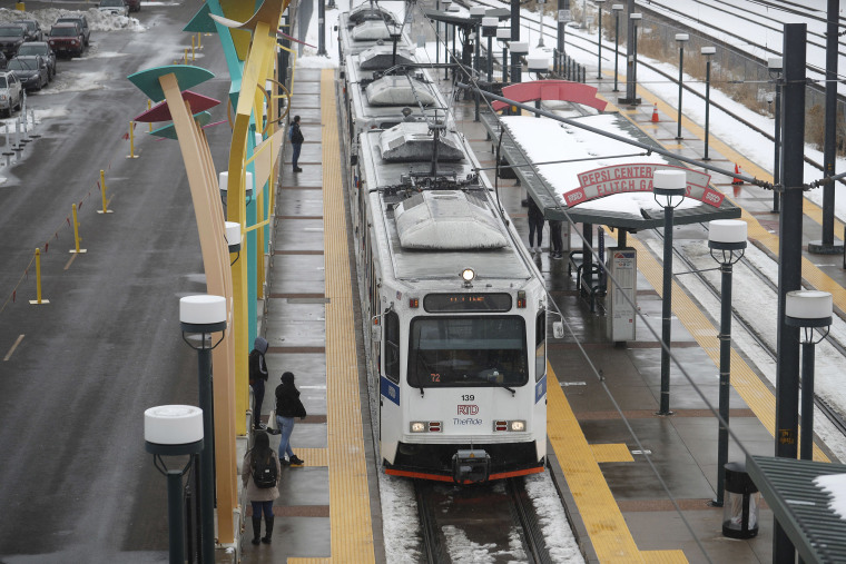 Image: Bundled up against cold temperatures and light snow, passengers wait for a light rail train to pull up to a station