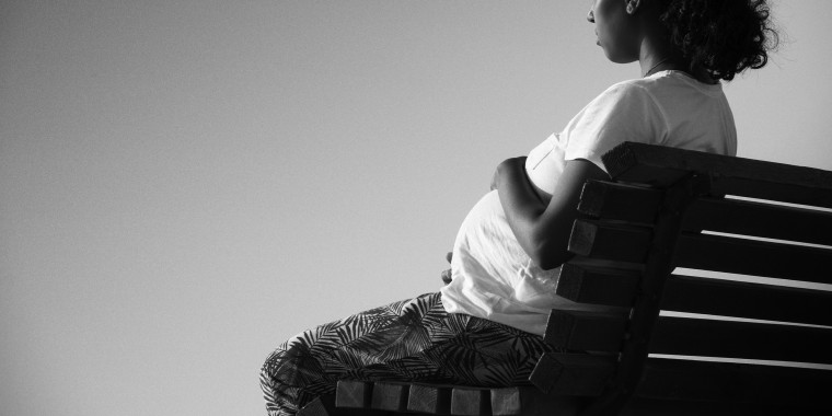 Image: a pregnant woman sitting on a bench.