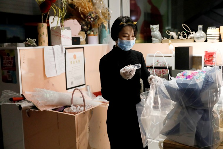 Image: A florist who prefers to be called Cai Xiaoman wearing a face mask and gloves, puts a bottle of hand sanitizer into a bouquet at a flowers shop in a shopping mall, as the country is hit by an outbreak of the new coronavirus, in Beijing