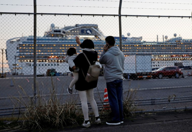 Image: Family members of passengers onboard the cruise ship Diamond Princess wave and talk to them on the phone at Daikoku Pier Cruise Terminal in Yokohama