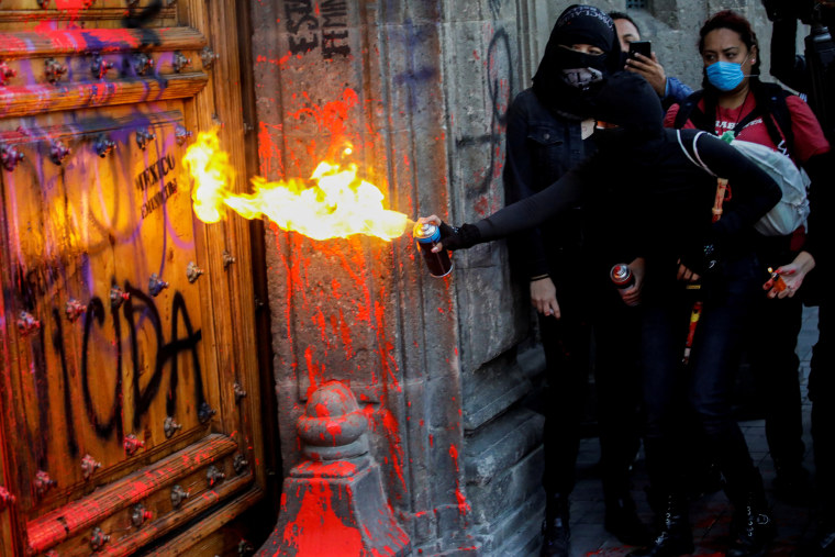 In Mexico, activists splash presidential palace red, protesting women's murders