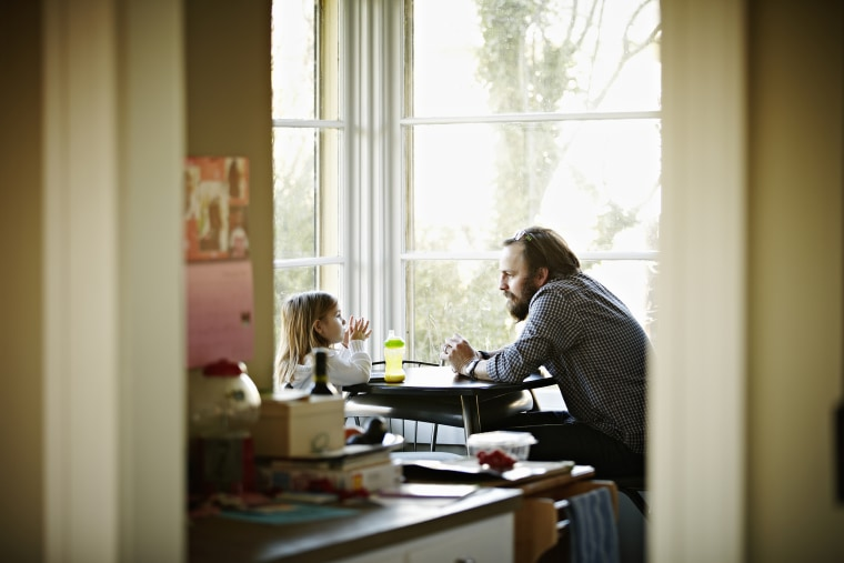 Image: Father and daughter sitting at table in discussion