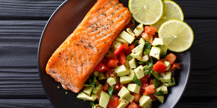 Fried salmon steak with avocado tomato salsa closeup on a plate. horizontal top view from above