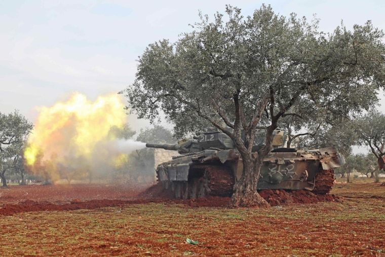 Image: Syrian rebel fighters fire from their position in the countryside of Idlib towards government forces positions