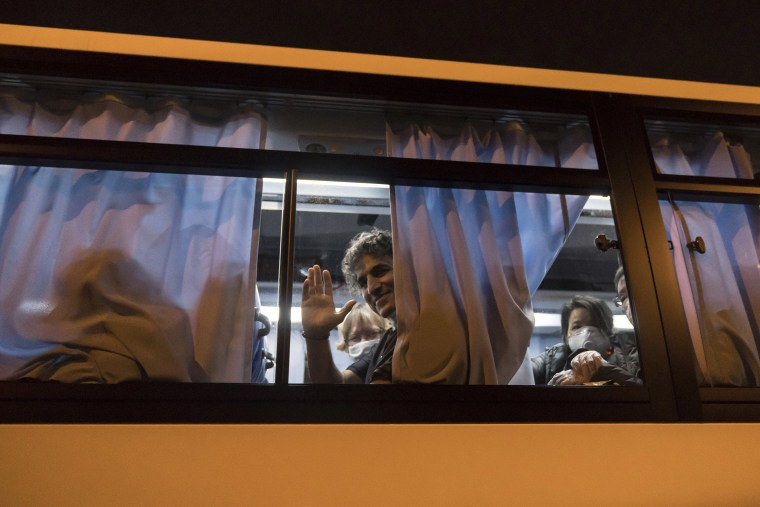 Image: An American citizen waves from a bus as he arrives at Haneda airport on Feb. 17, 2020 in Tokyo, Japan.