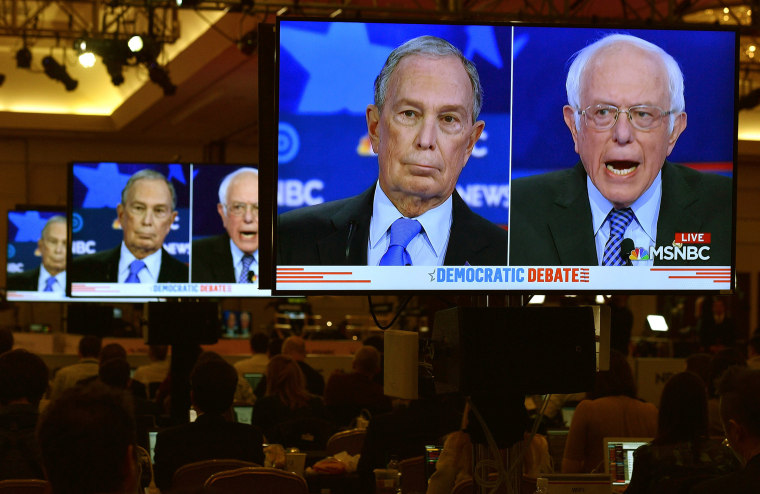 Image: Mike Bloomberg and Senator Bernie Sanders on video screens in the media filing center during the ninth Democratic 2020 U.S. Presidential candidates debate at the Paris Theater in Las Vegas