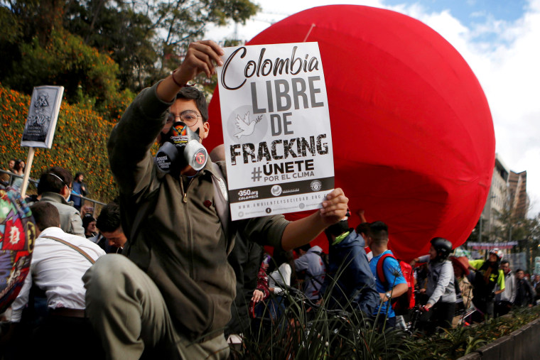 """Image: An activist holds a sign that reads """"Colombia free of fracking"""" during a climate change protest in Bogota, Colombia, on Sept. 8, 2018."""