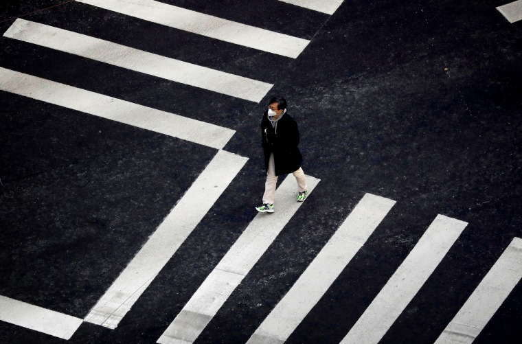 Image: A man wearing a protective mask crosses the street in Seoul on Feb. 20, 2020.
