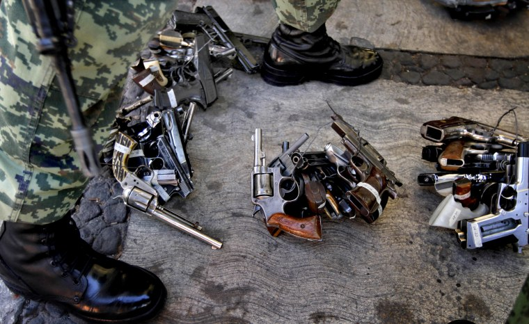 Image: A soldier stands near weapons given to the government in exchange for goods or money in Mexico City on Dec. 30, 2012.