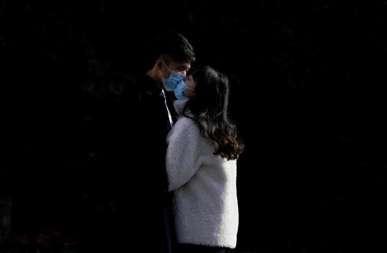 Image: A couple wearing masks kiss at a main shopping area, in downtown Shanghai
