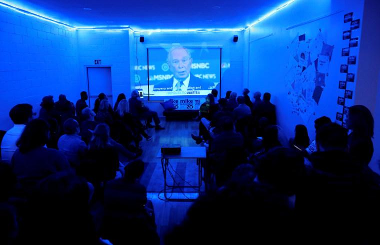 Image: Campaign workers watch Mike Bloomberg speak at Democratic debate in New York on Feb. 19. 2020.
