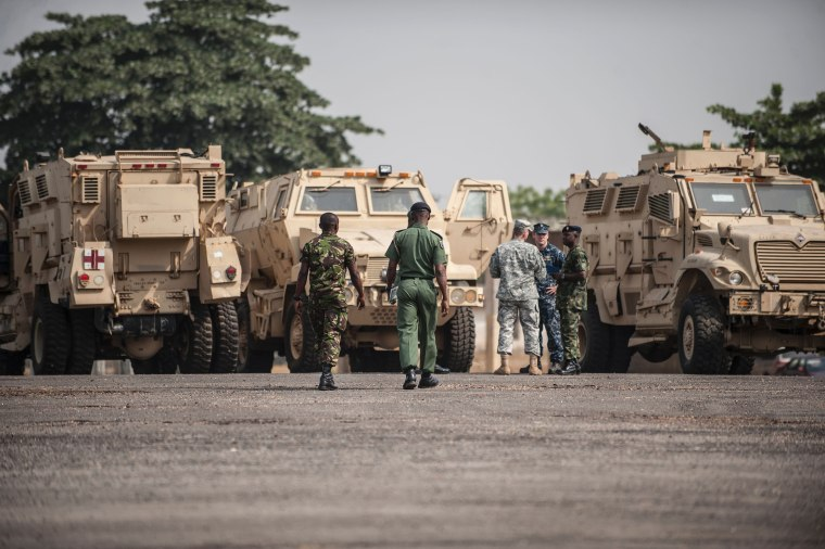 Members of the Nigerian and United States military next to some of the 24 armored vehicles donated to the Nigerian government