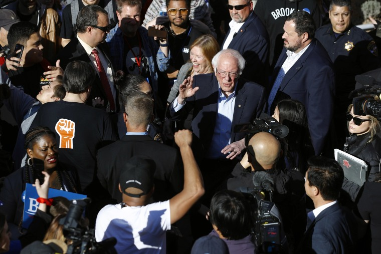 Image: Democratic presidential candidate Sen. Bernie Sanders, I-Vt., and his wife Jane O'Meara Sanders lead supporters to an early voting location after a campaign event at the University of Nevada, Las Vegas