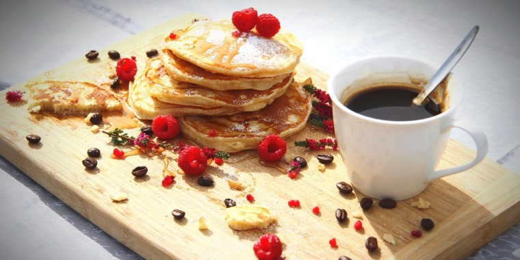 High Angle View Of Pancakes With Black Coffee On Cutting Board Served On Table