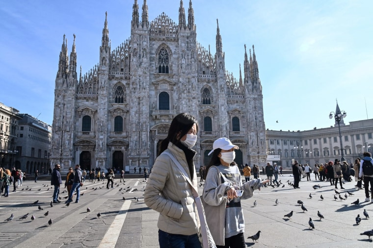 Two women wearing masks walk across the Piazza del Duomo in central Milan, on Feb. 24, 2020.