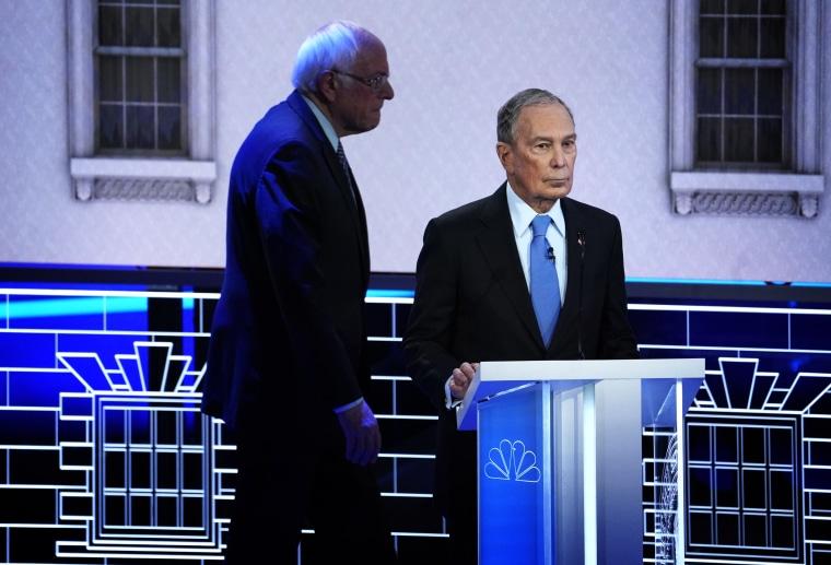 Image: Sen. Bernie Sanders walks behind Mike Bloomberg at a Democratic presidential primary debate in Las Vegas on Feb. 19, 2020.