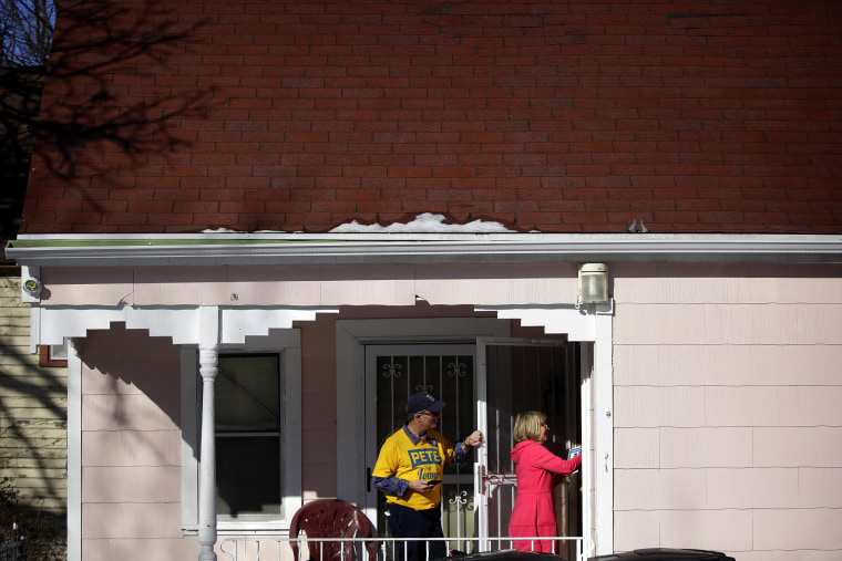 Image: Len Edgerly and Darlene Determan knock on a door while canvasing for Pete Buttigieg in Des Moines, Iowa, on Feb. 2, 2020.