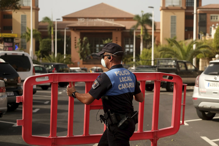Image: A Spanish police officer sets a barrier blocking the access to the H10 Costa Adeje Palace hotel in Tenerife, Canary Islands, Spain