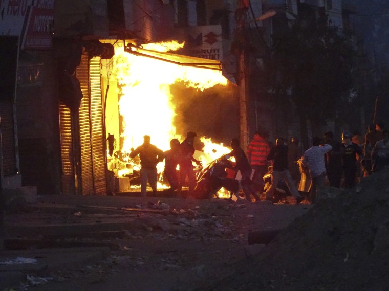 Image: A shop burns as a mob sets it on fire during violence between two groups in New Delhi, India
