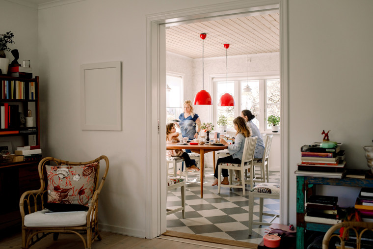 Mothers and daughters having breakfast at dining table seen through doorway