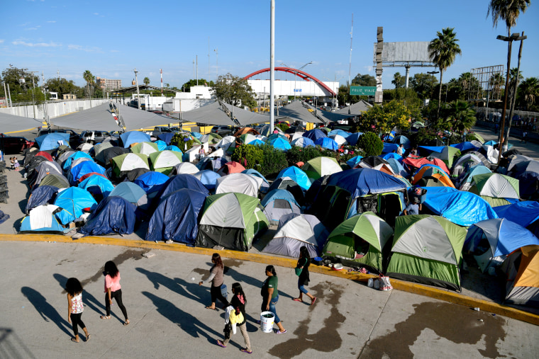 "Image: FILE PHOTO: Migrants, most of them asylum seekers sent back to Mexico from the U.S. under the ""Remain in Mexico"" program officially named Migrant Protection Protocols (MPP), occupy a makeshift encampment in Matamoros"