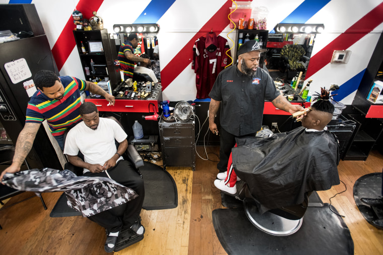 Image: ReCarlo Lewis, owner of Lucciono's barbershop, second right, and Eldred Anderson, left, attend to clients in North Charleston, S.C.