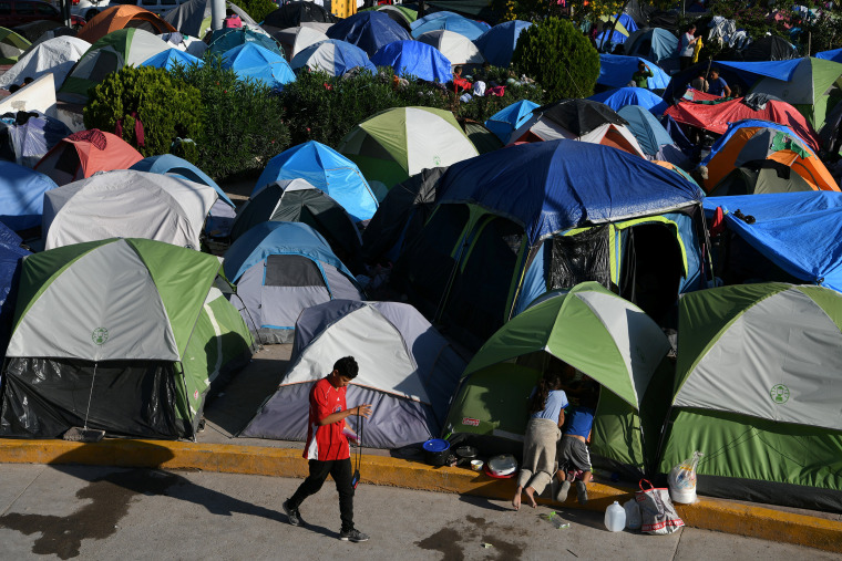 "Image: Migrants, most of them asylum seekers sent back to Mexico from the U.S. under the ""Remain in Mexico"" program officially named Migrant Protection Protocols (MPP), occupy a makeshift encampment in Matamoros"