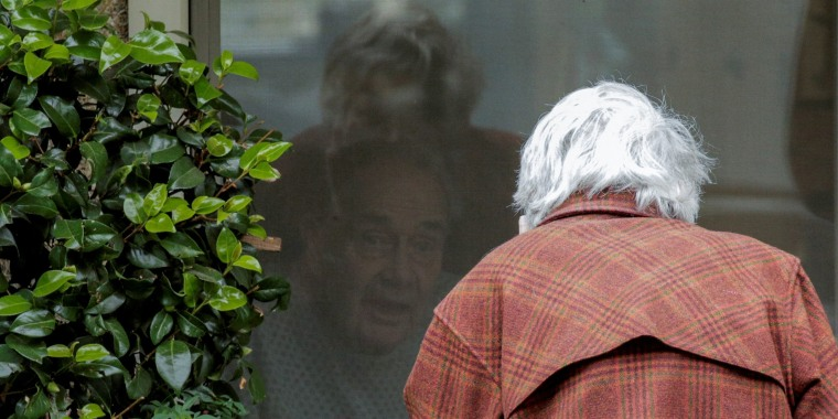 Image: Gene Campbell talks through a window with his wife of more than 60 years, Dorothy Campbell, at the Life Care Center of Kirkland, the long-term care facility linked to several confirmed coronavirus cases in the state, in Kirkland