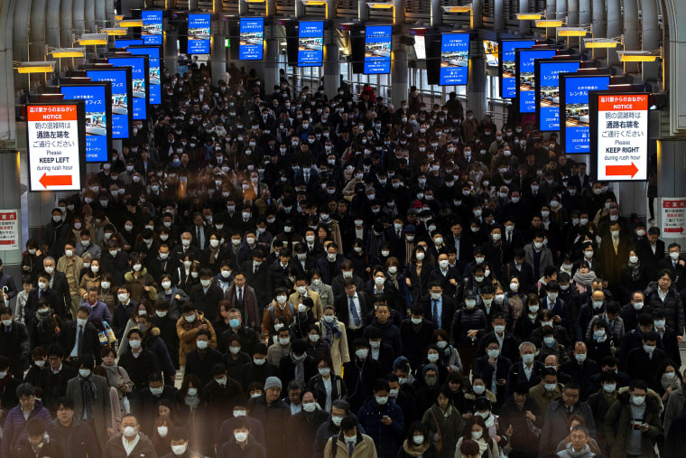 Image: Crowds wearing protective masks, following an outbreak of the coronavirus, are seen at the Shinagawa station in Tokyo