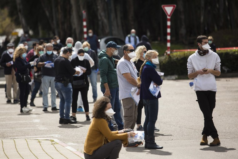 Image: Israelis in isolation due to Coronavirus concerns attend to cast their vote in a sterile polling tent
