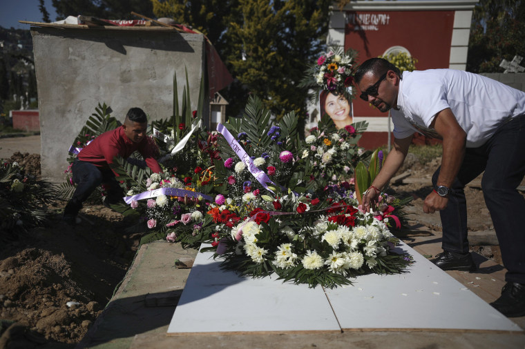 Image: Juan, right, who has been arrested in connection with the disappearance and murder of Marbella Valdez, puts a floral arrangement on her grave, alongside her ex-boyfriend Jairo Solano, during her funeral at a cemetery in Tijuana, Mexico