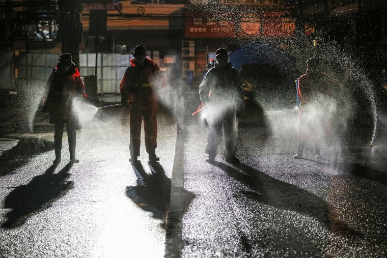 Image: Workers spraying disinfectant on a road in Yunmeng county, Xiaogan city, in China's central Hubei province