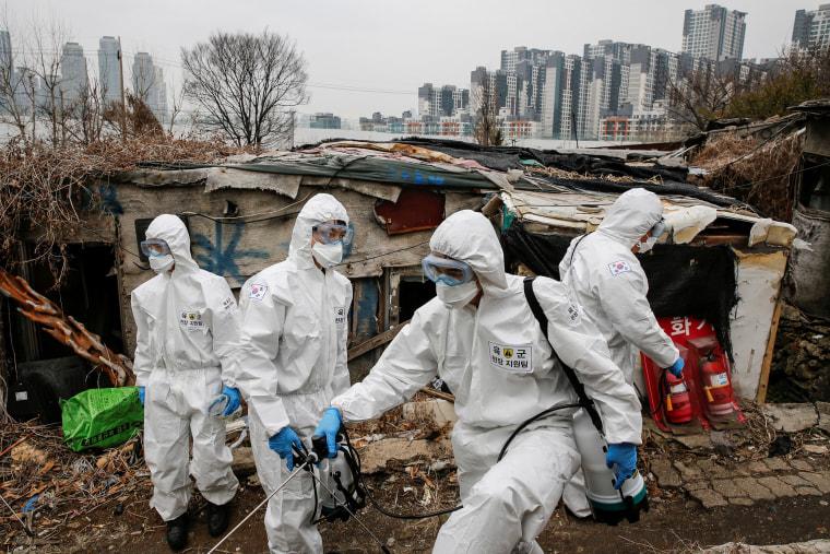 Imagen: Soldados surcoreanos en engranajes protectores desinfectan las chozas mientras se ve un lujoso complejo de apartamentos de gran altura en el fondo en la aldea de Guryong en Seúl